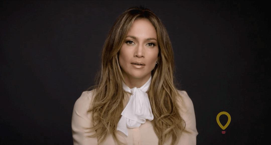 Jennifer Lopez speaks against a dark background.