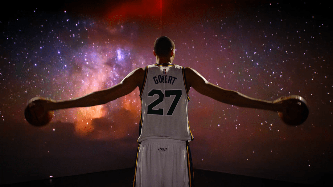 This Utah Jazz promo features multiple players from the basketball team in front of an array of projections.