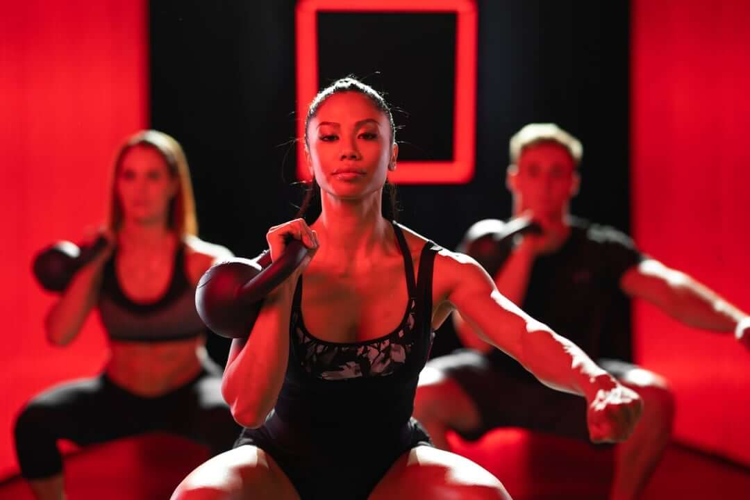 This VASA studio commercial features individuals working out with weights and bikes on a set completely lit with red.