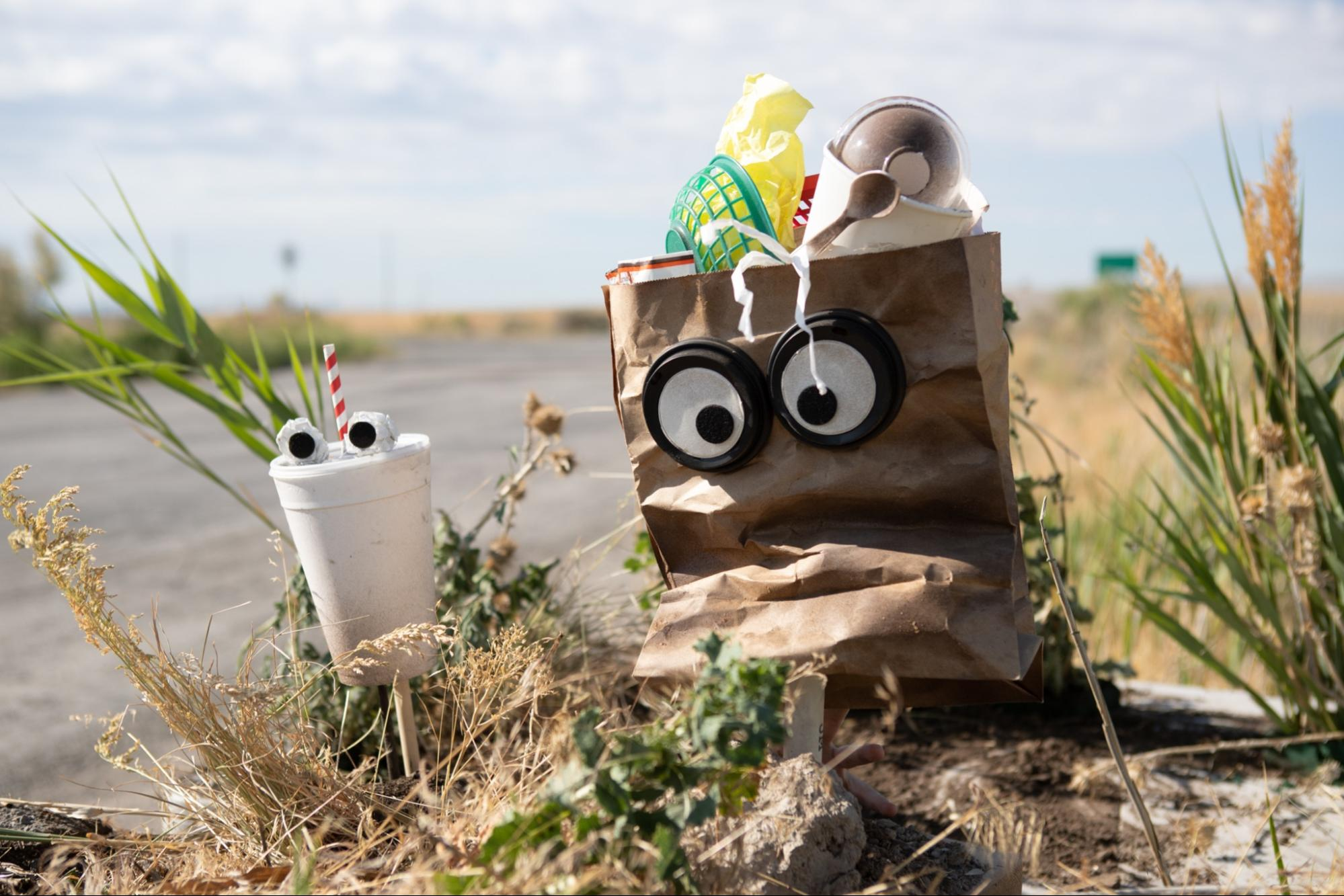 a bag and a cup puppet on the side of the road.
