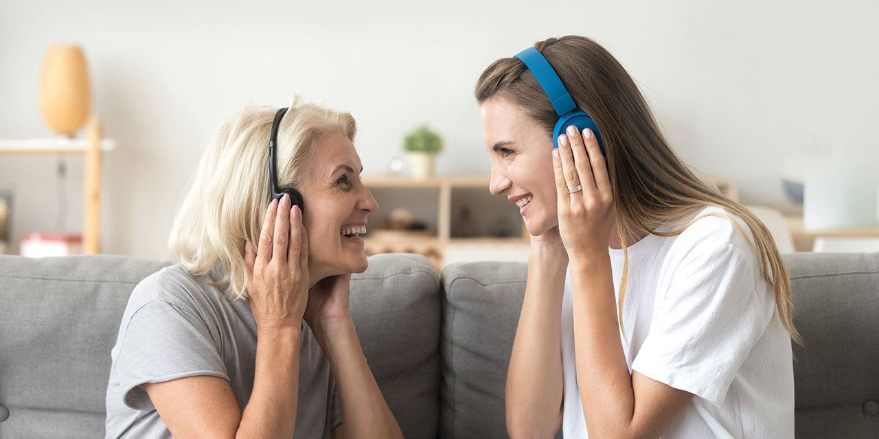 Image shows two women with headphones on. They are looking at each other and smiling.