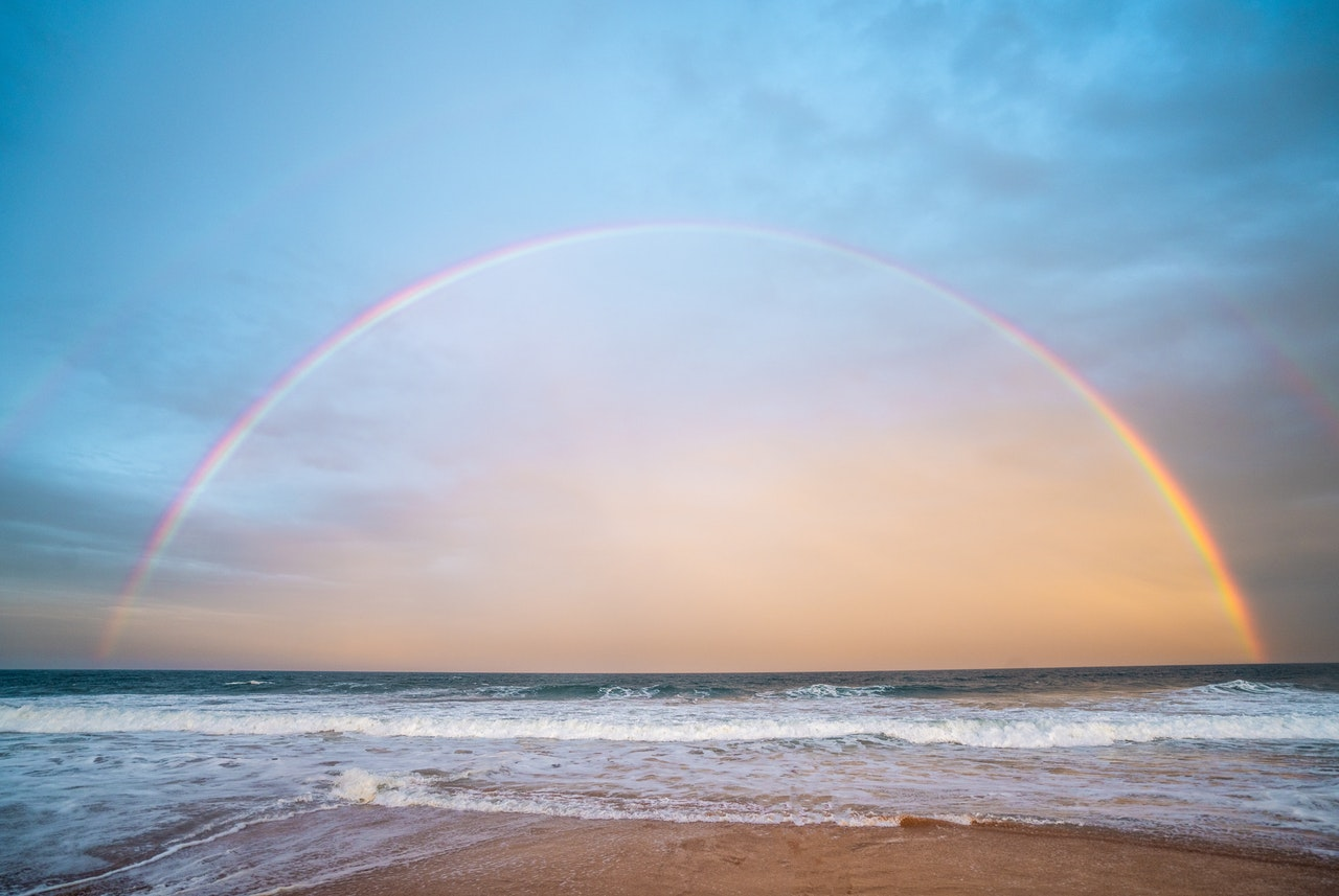Photograph of a whole rainbow over the sea with waves on the beach in the foreground