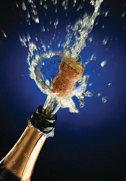 A cork bursts from the neck of a celebratory bottle