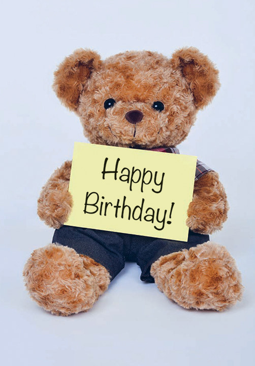 A teddy bear holding a note saying Happy Birthday