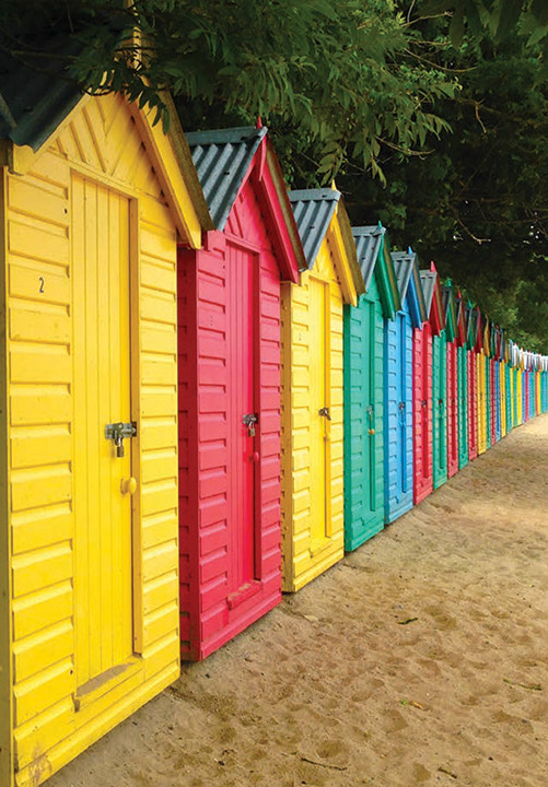 A photograph of a row of brightly coloured beach huts standing on a sandy beach