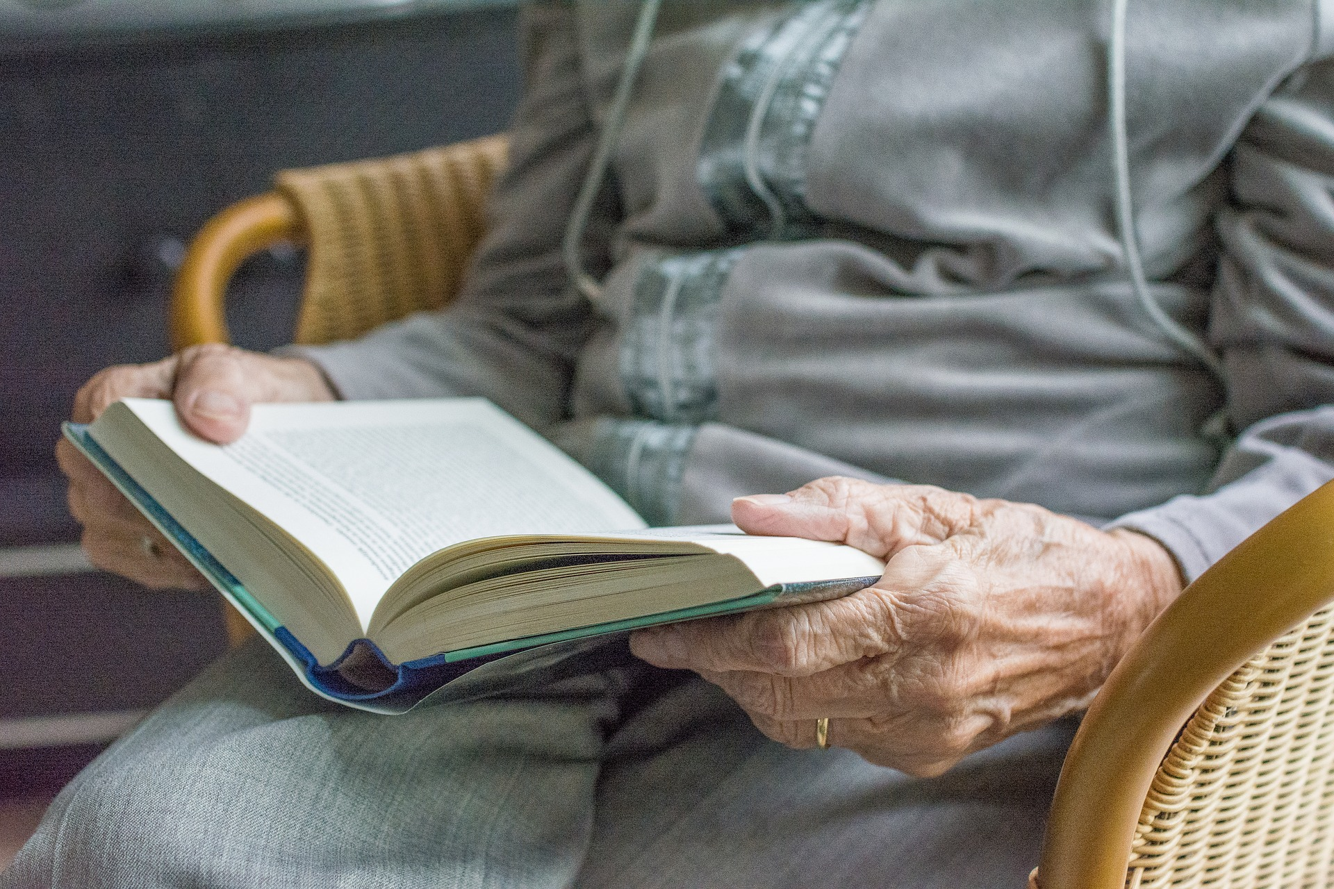 Image shows a lady sitting in a chair reading.