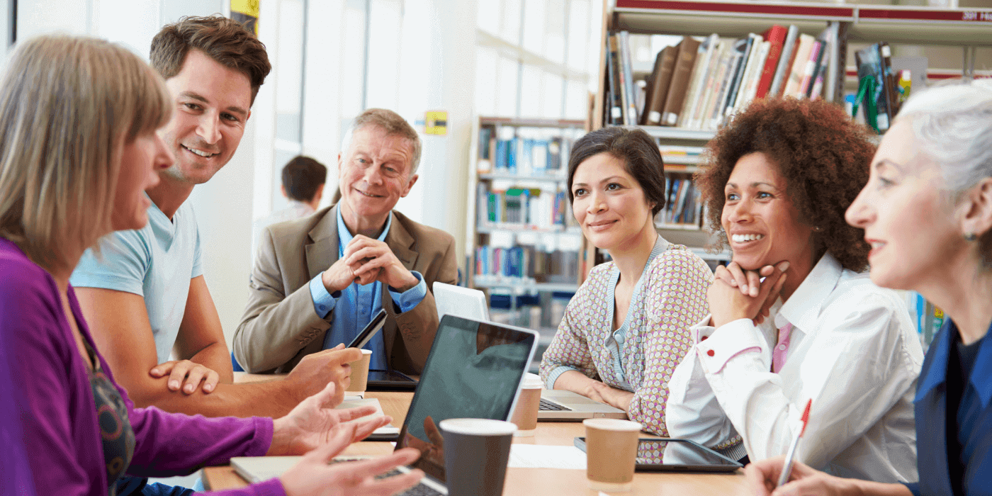 Group of 6 people sitting around a table at a library smiling