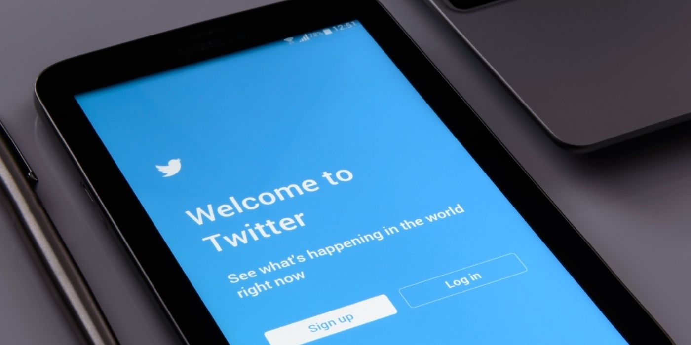 Mobile phone on a desk showing the Twitter login screen