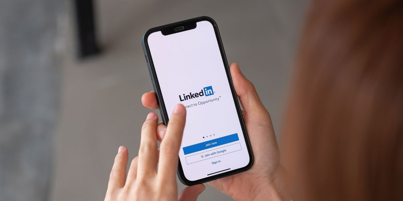 Mobile phone in a hand showing the LinkedIn login screen