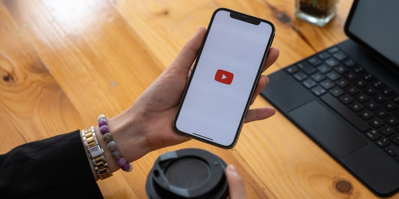 Mobile phone on a desk showing the Youtube logo