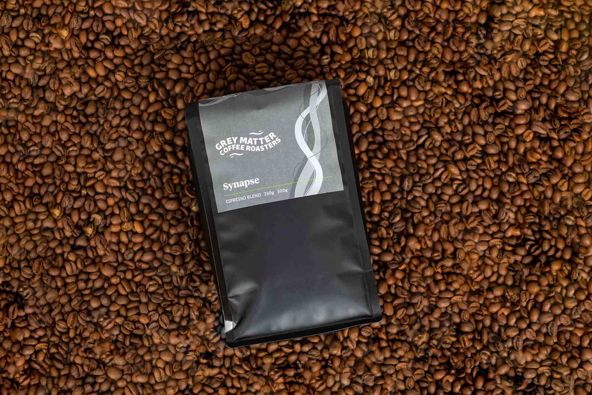 The Grey Matter Coffee Roaster logo in use on packaging against a backdrop of coffee beans.