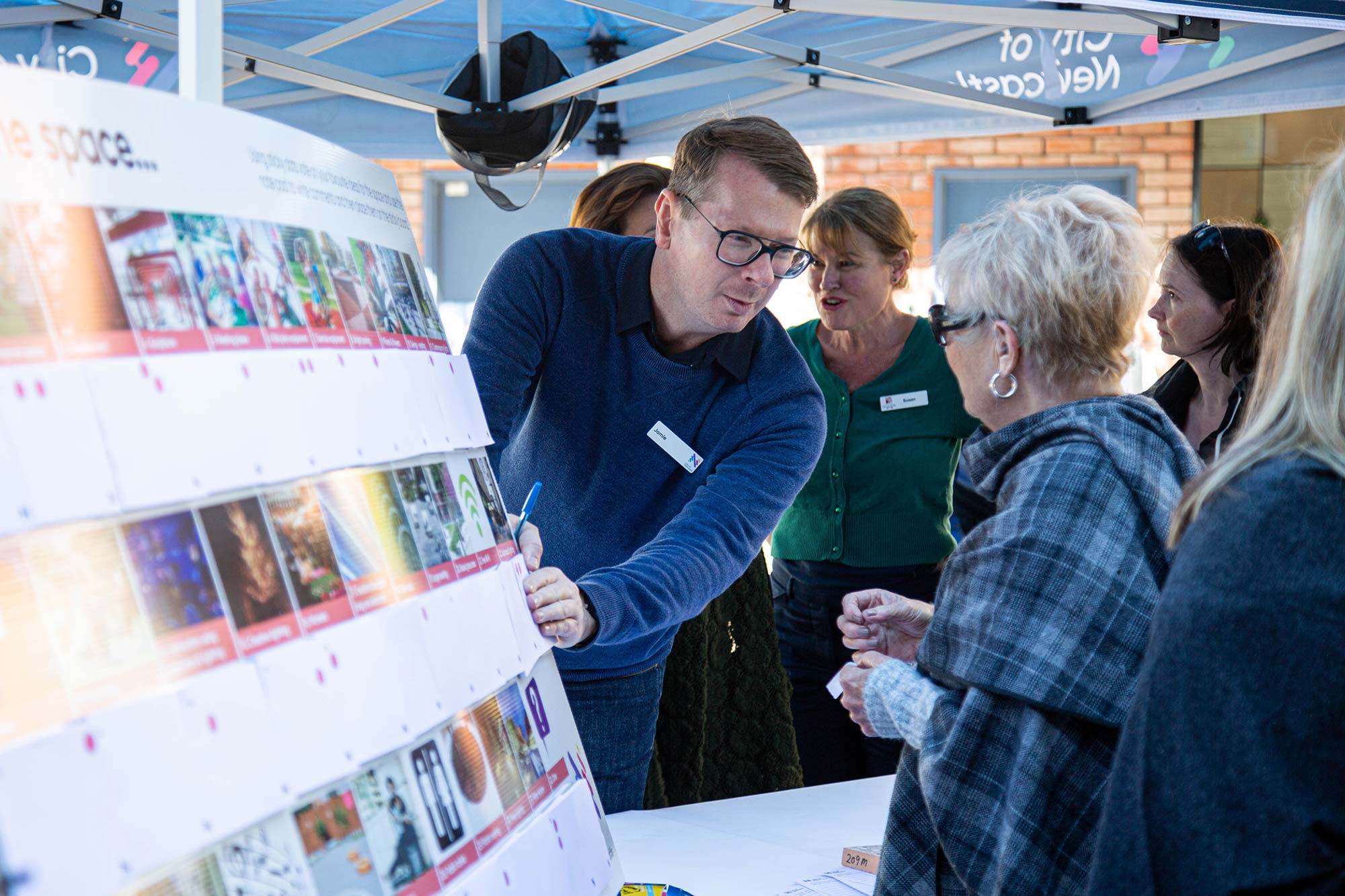 Photography for the City of Newcastle, a man explains to a lady in Hamilton about city plans.