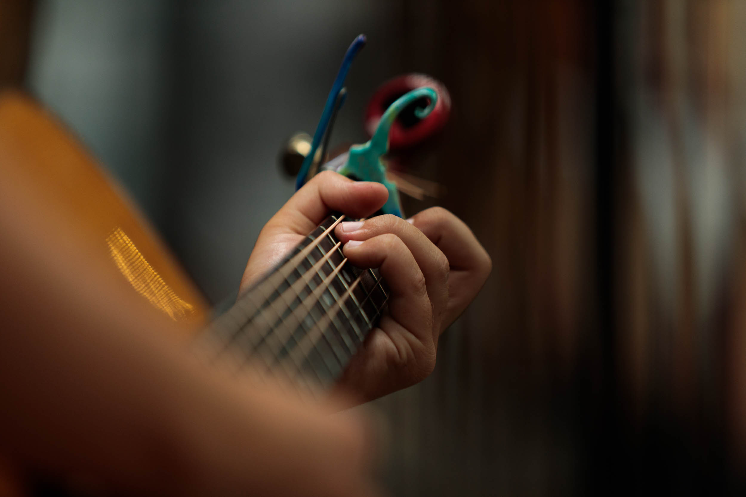 A musician holding a chord on a guitar