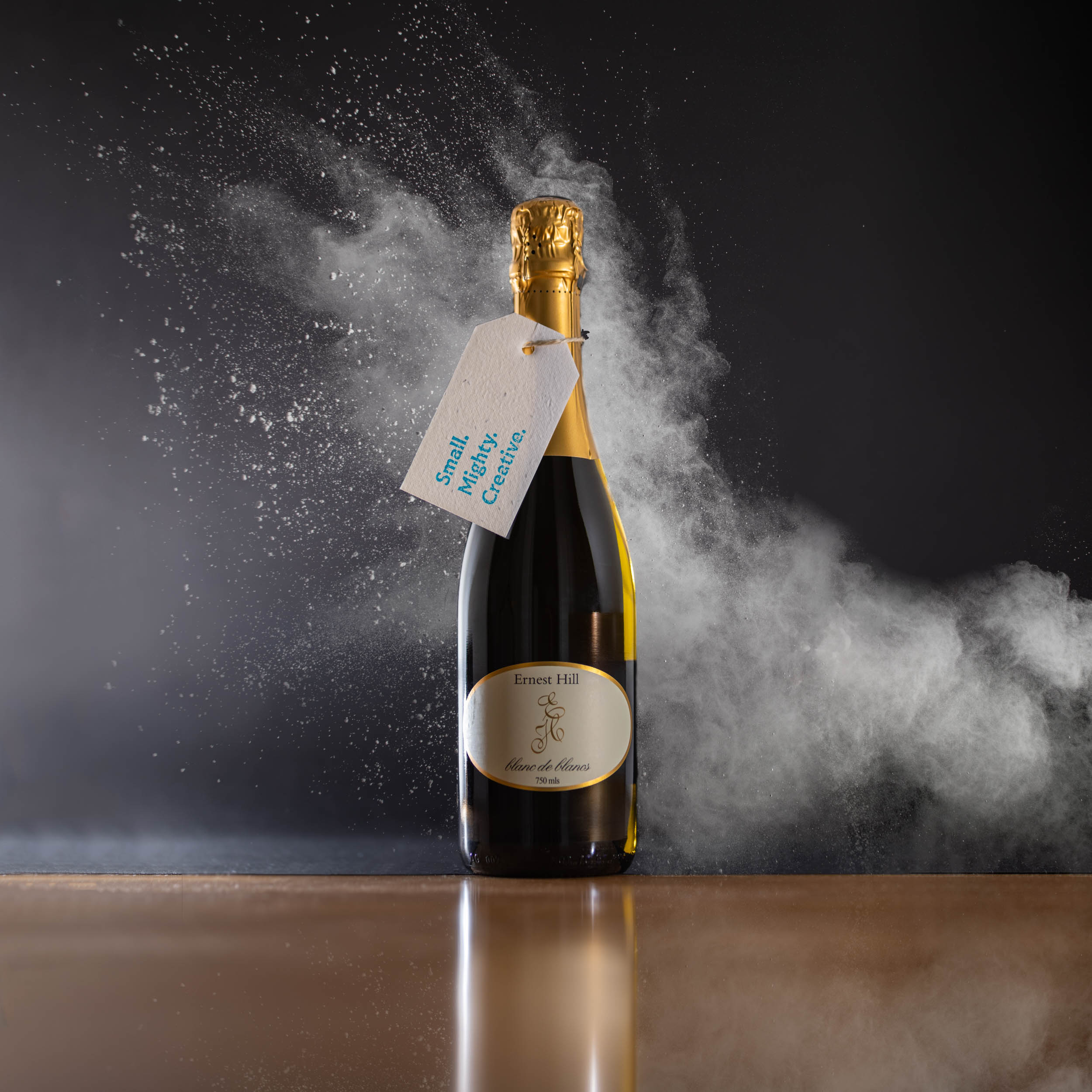Ernest Hill Sparkling wine bottle with a gift tag attached, with an exploding of foam behind it