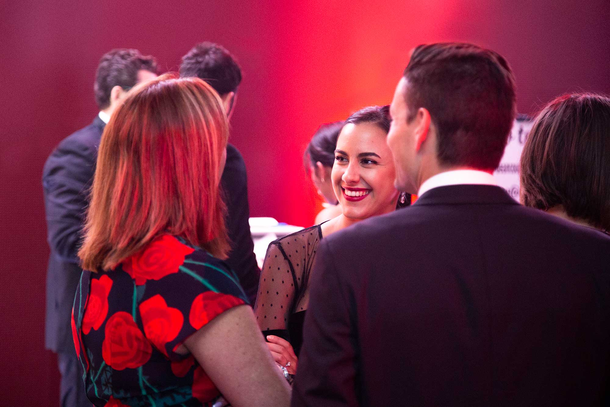An action photograph of three people having a conversation at a Bean Counters Ball event.
