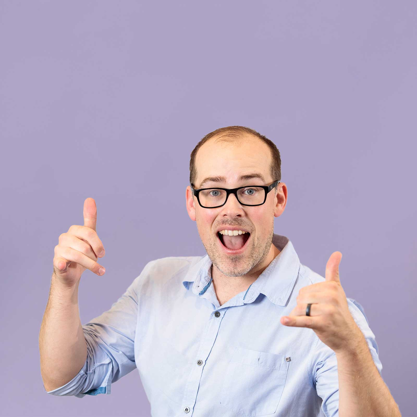 A portrait of Martin Sully, a man with glasses holds his hands out and has his thumbs up. He's against a purple background.