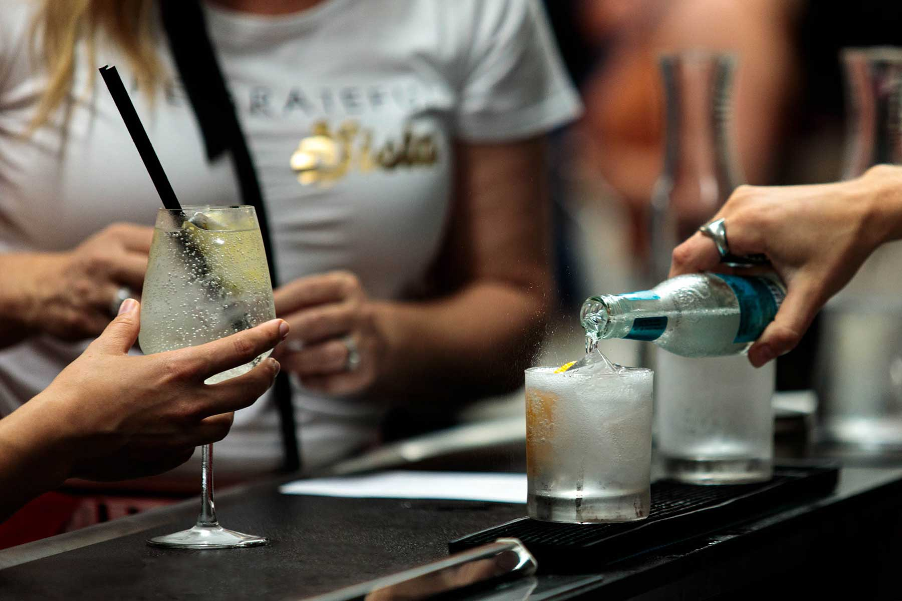 a hand pours a gin and tonic at a bar, while a customer waits