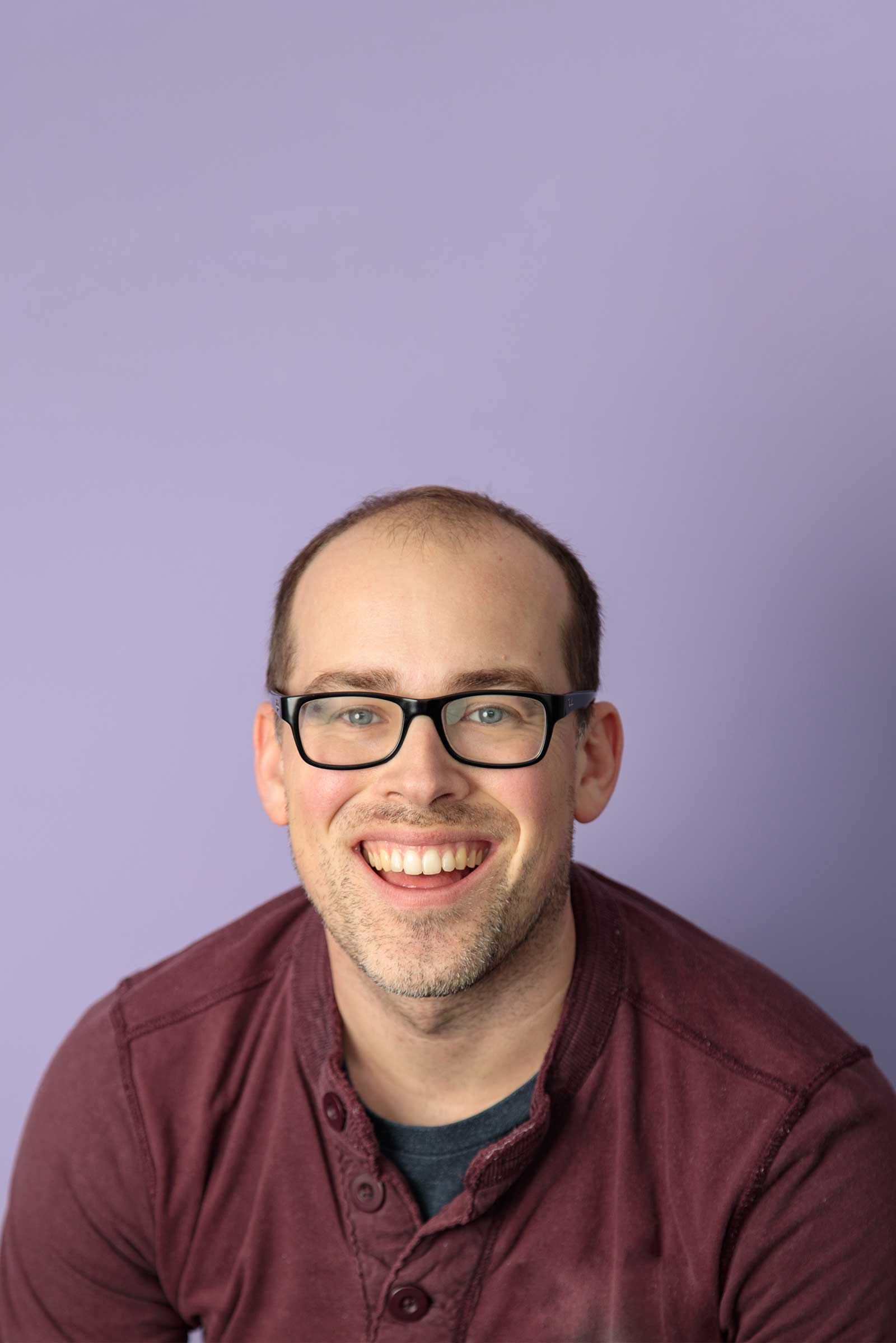 A portrait of a man in a maroon sweater agains a purple backdrop.