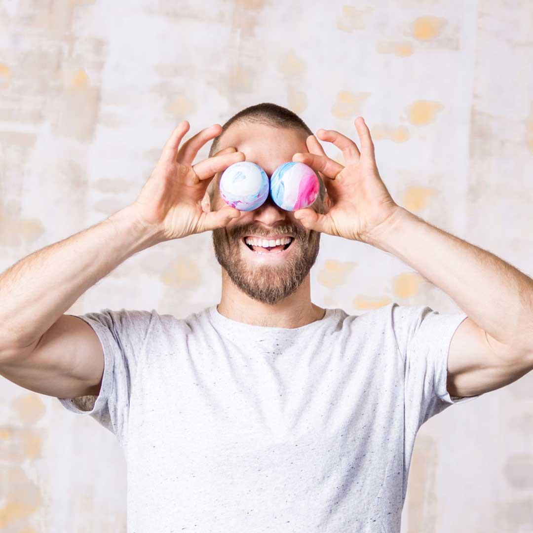 a smiling man holds to lacrosse balls to his face pretending that they are his glasses