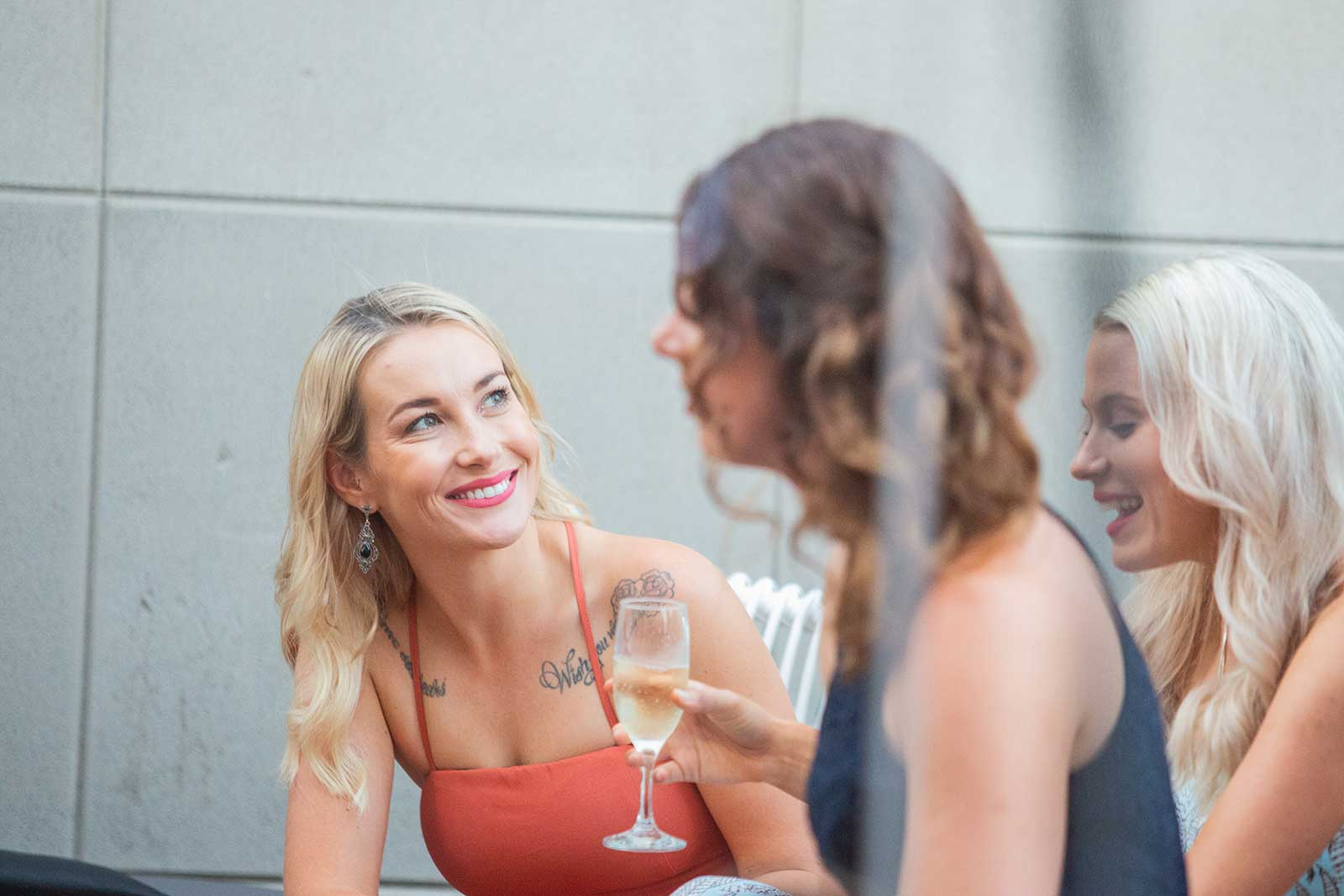 A girls in a dress smiles at friends as they drink champagne