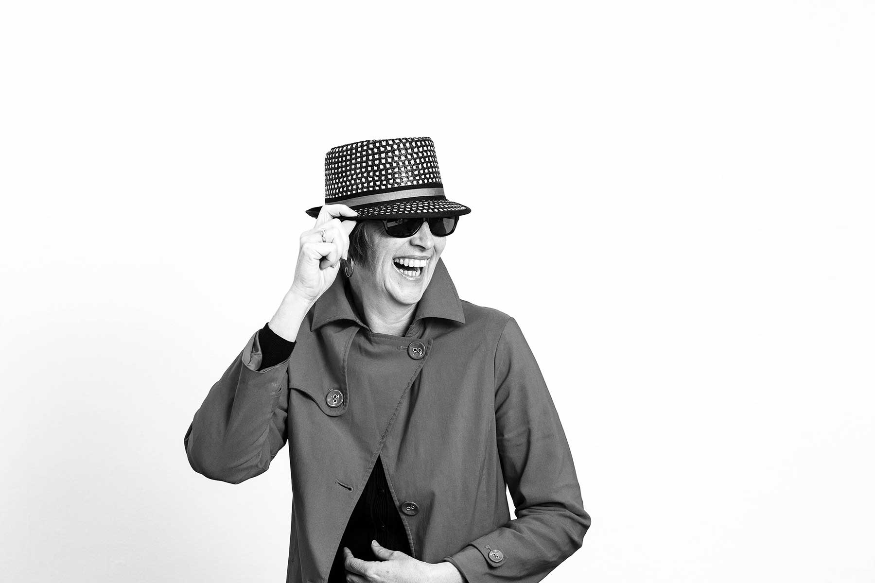 a laughing lady on white background in a trench coat with a hat and sunglasses on