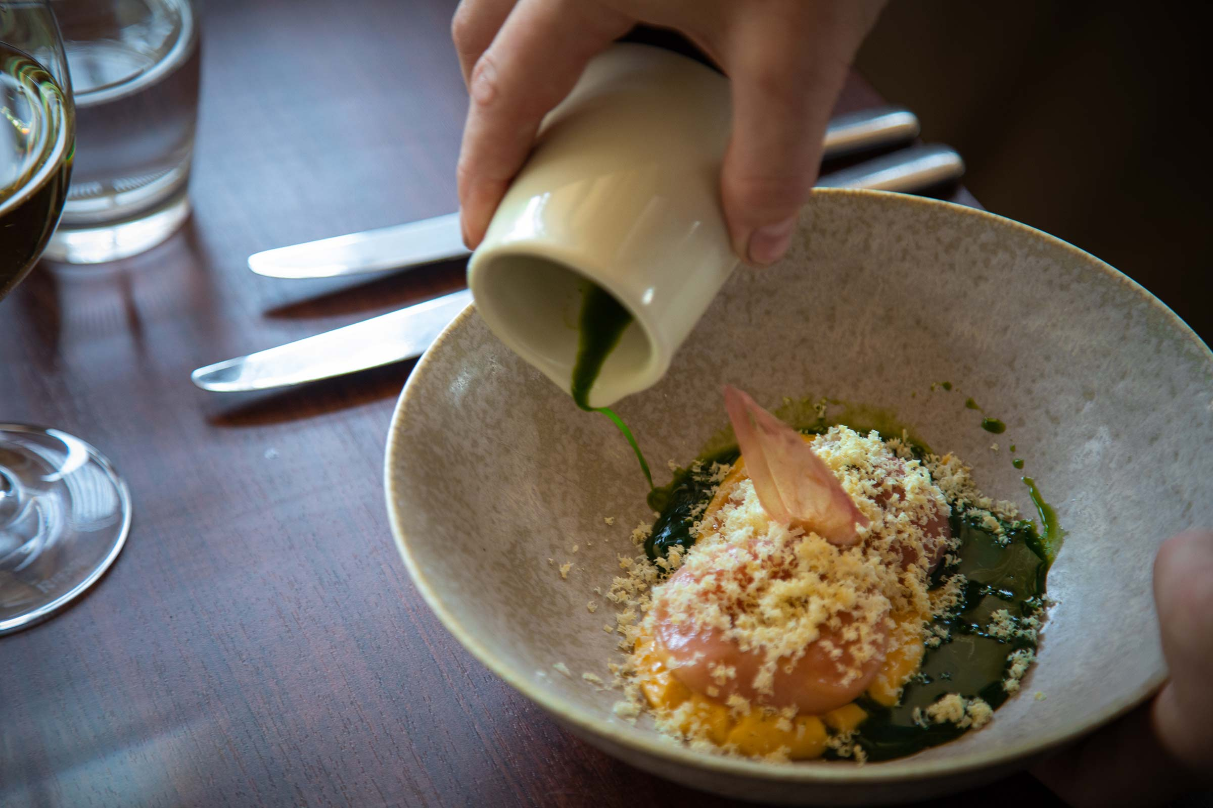 A green sauce is being poured onto a peach in a restaurant