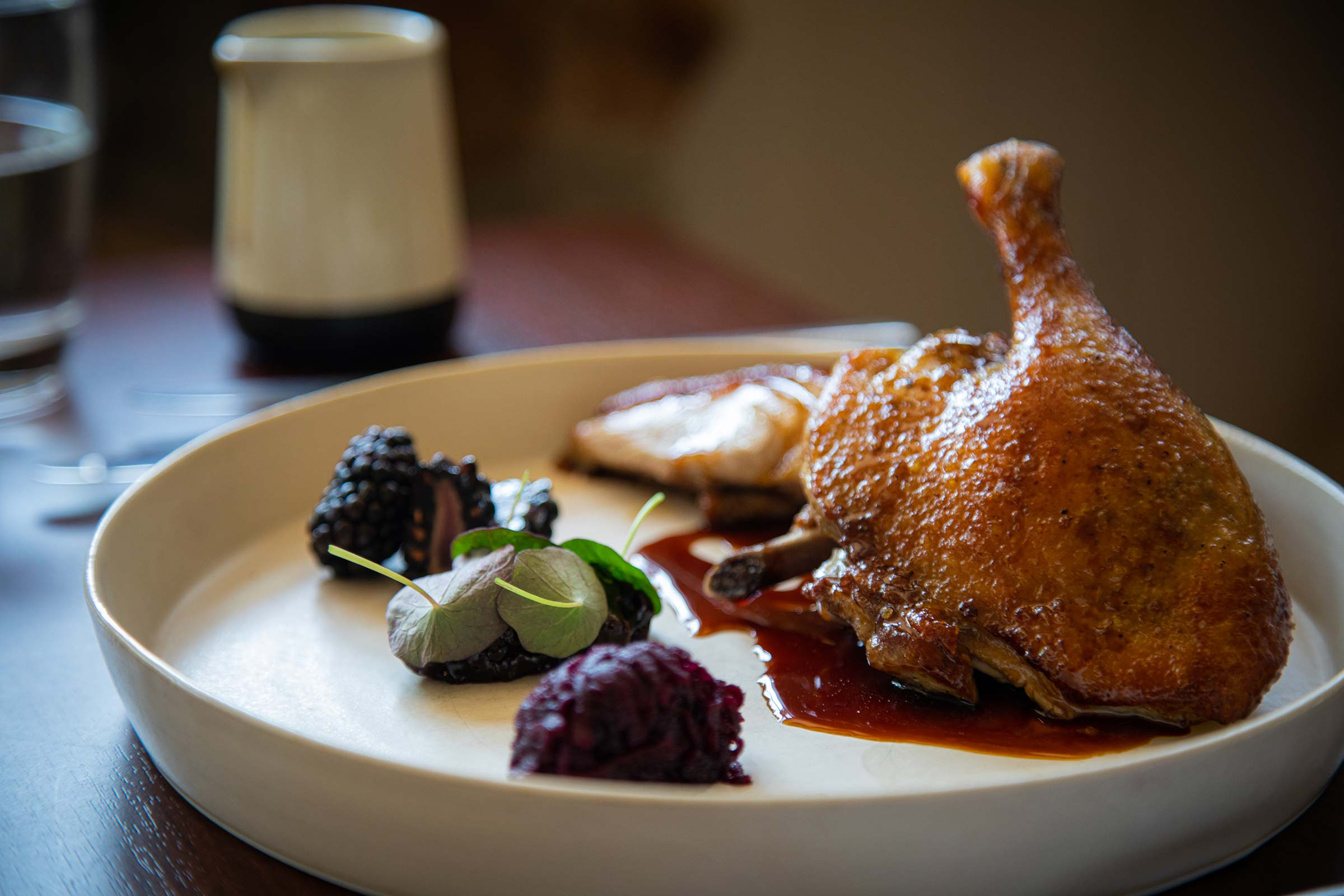 A roast chicken leg on a white plate with blackberries