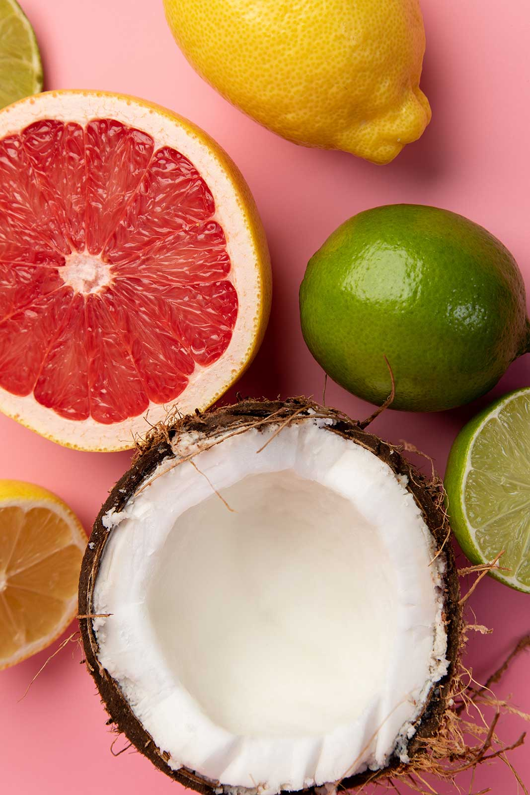 a pink grapefruit, an open coconut, a lemon and limes are photographed against a pink background