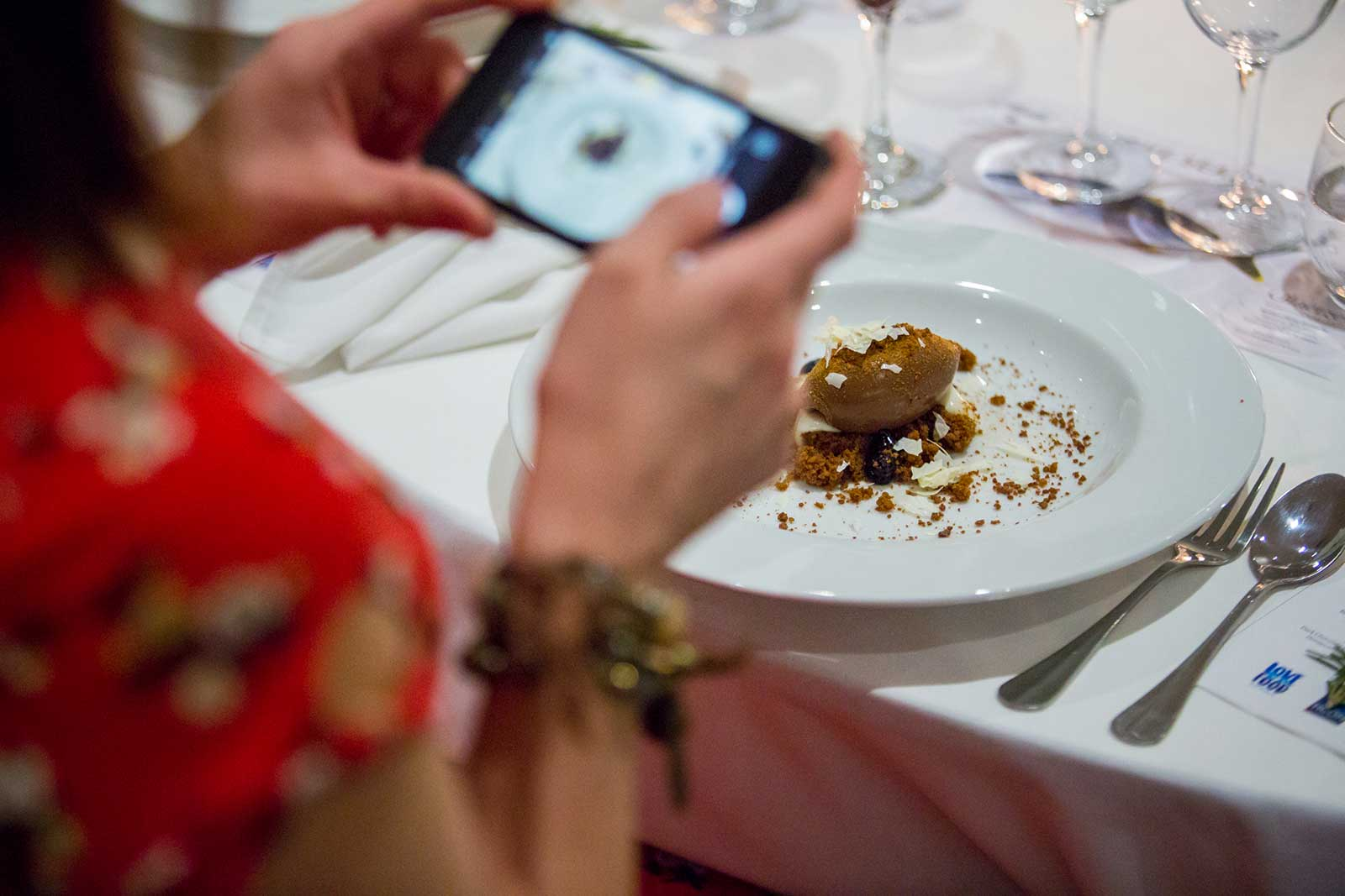 a girl in a red dress photographs her food, the photo focuses on the food and her camera is blurred