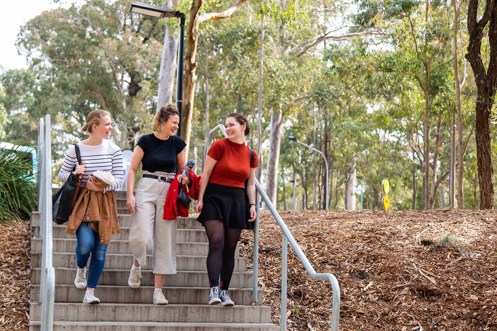 3 girls walk down a set of steps in the bushland of the University of Newcastle campus. They are looking at each other smiling.