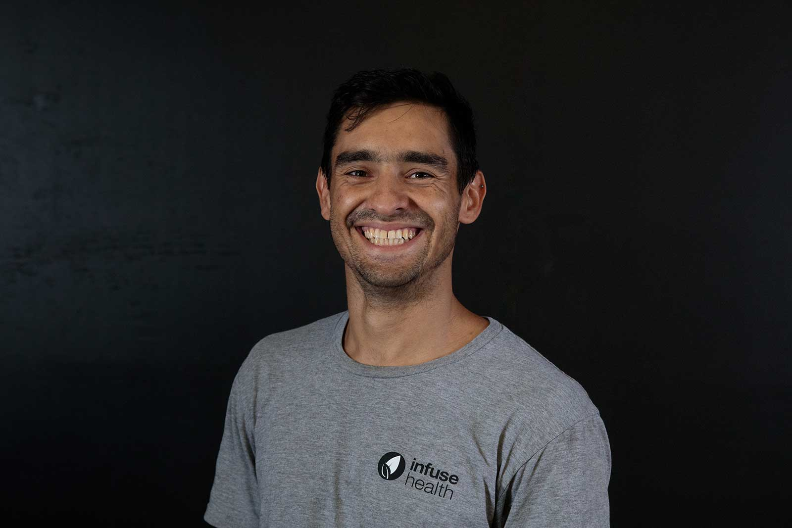 Elias Trotti, a movement instructor at infuse health, smiles back at the camera for his headshot