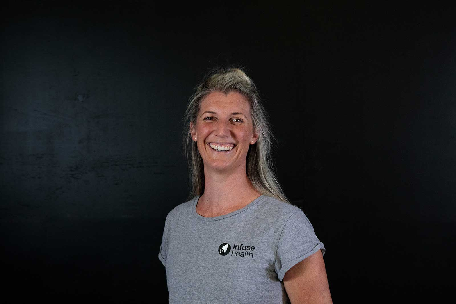 a lady smiles right back at the camera. She wears a grey t-shirt with an infuse health logo on it, she is stood against a black wall