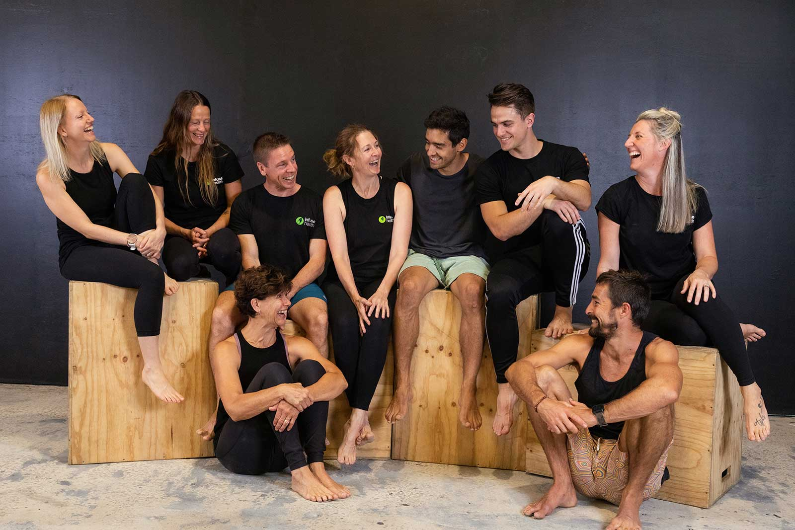 a group photograph of 9 people sat on boxes or the floor, they are all looking at one another and smiling or laughing