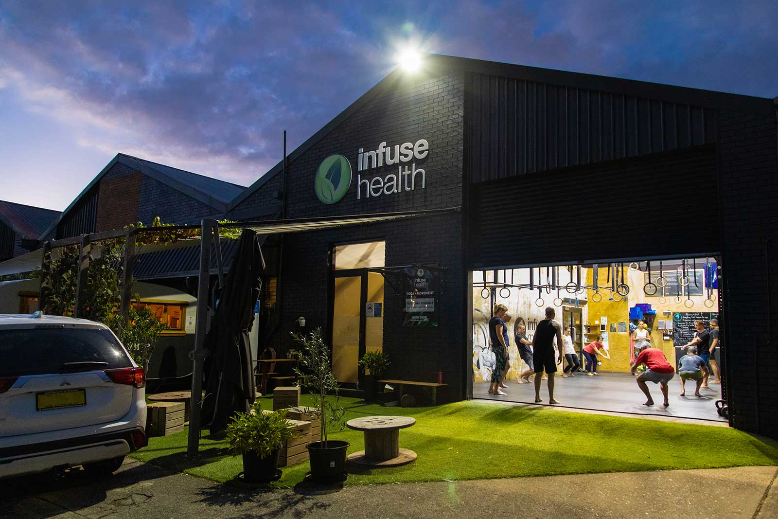 Infuse health exterior photograph at sunrise. A gym class is taking place through a roller door