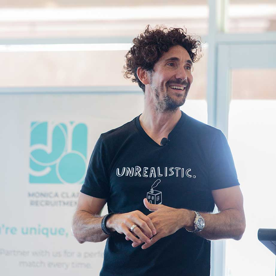 Gus Balbontin speaking at a Newcastle Business Club event, in a black t-shirt with Unrealistic written in white writing on it