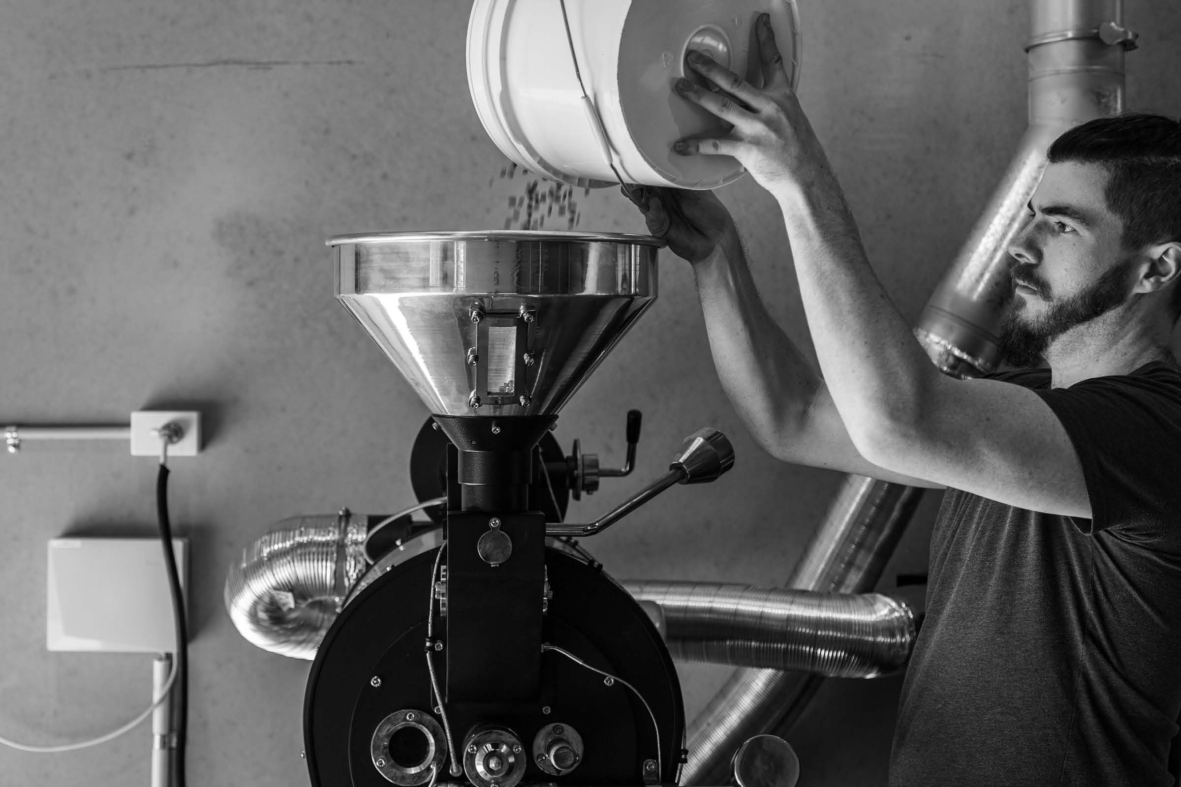 corporate photo of a man pouring coffee beans into the roaster.