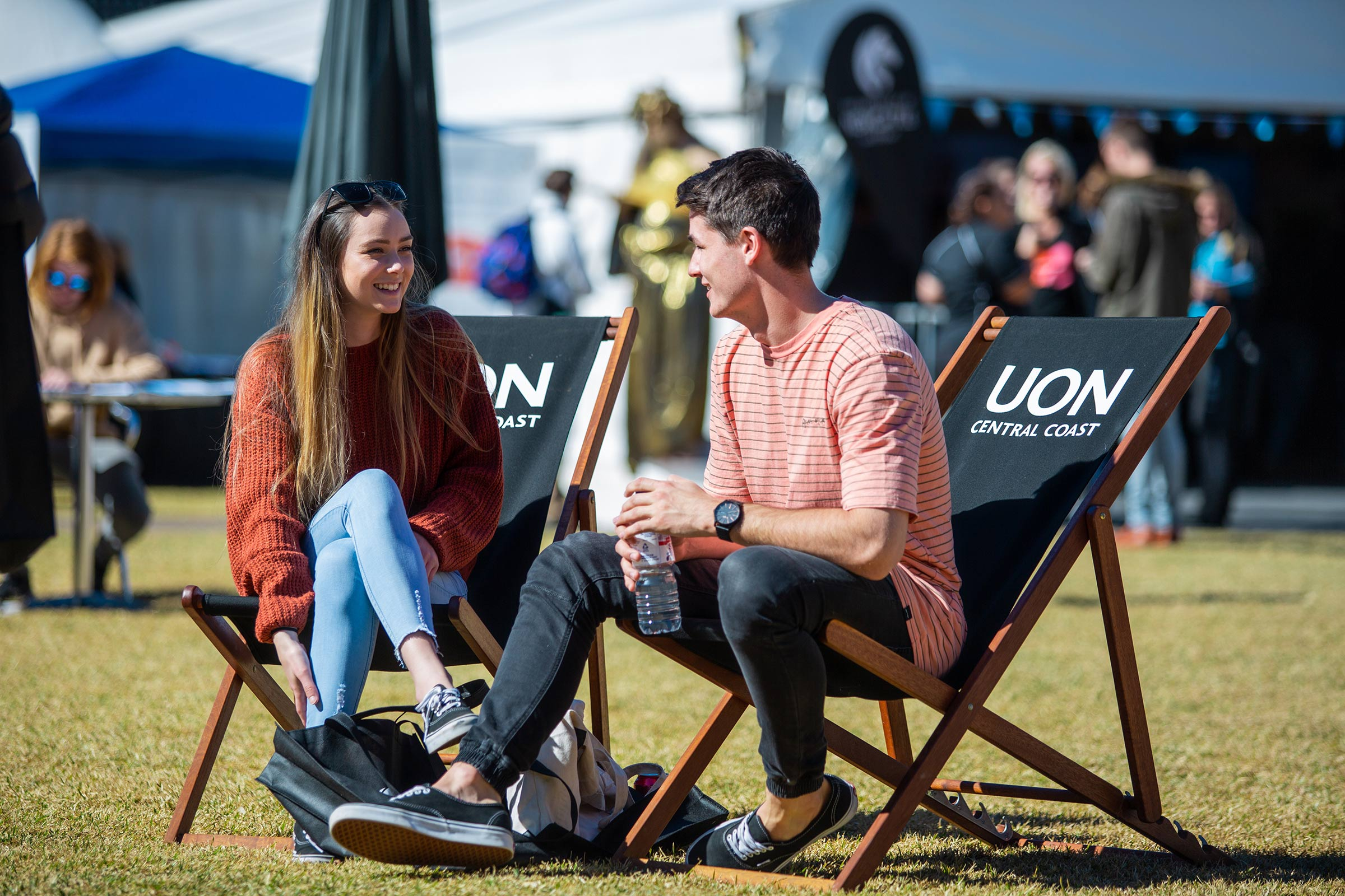 a photo of two relaxed students on deck chairs at the UoN Ourimbah campus on the central coast open day