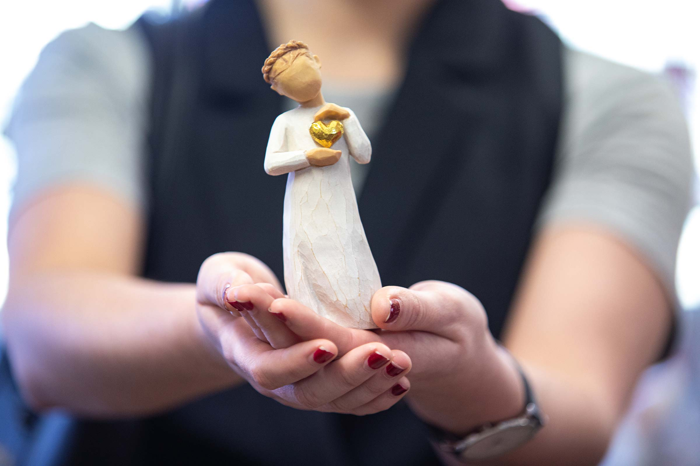 hands holding a porcelain figure. A photograph created by us to promote a shop in the Hunter Valley Shopping Village