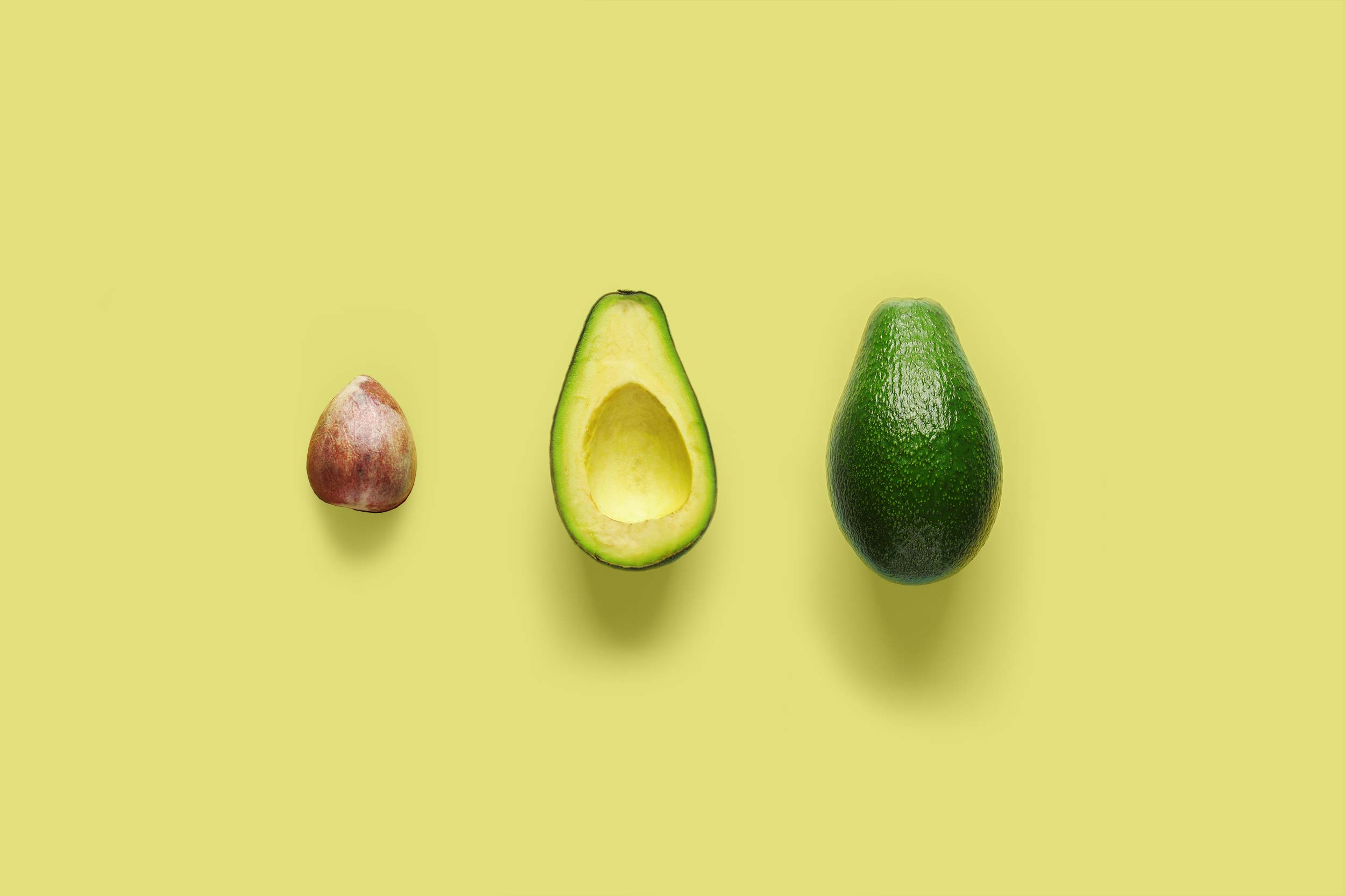The seed of an avocado, the flesh in the skin of an avocado and a whole avocado