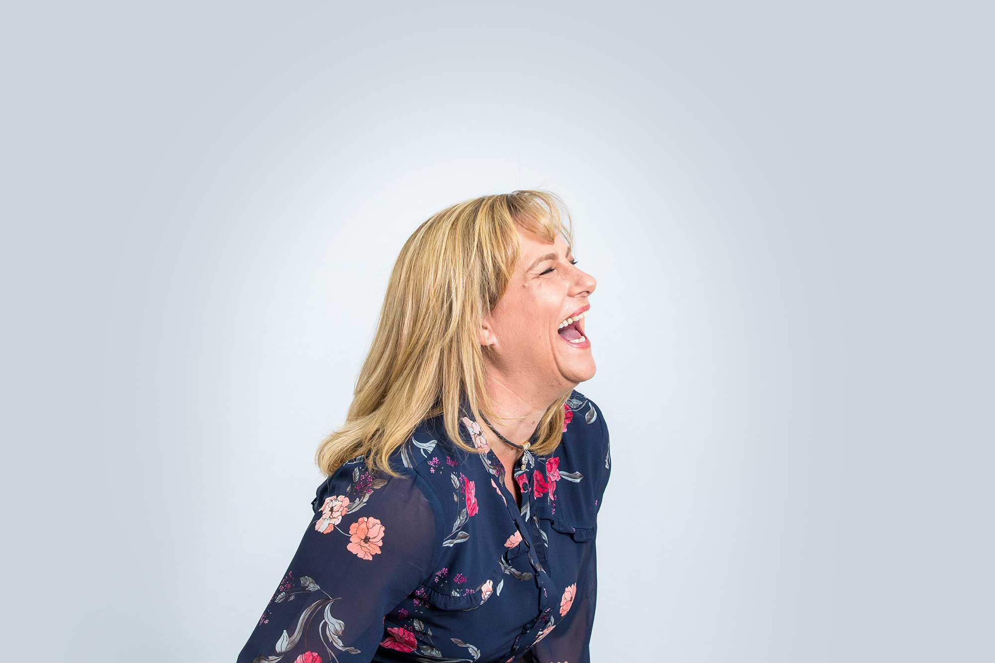 A lady in a navy shirt with a colourful floral pattern on it, laughs against an off white background