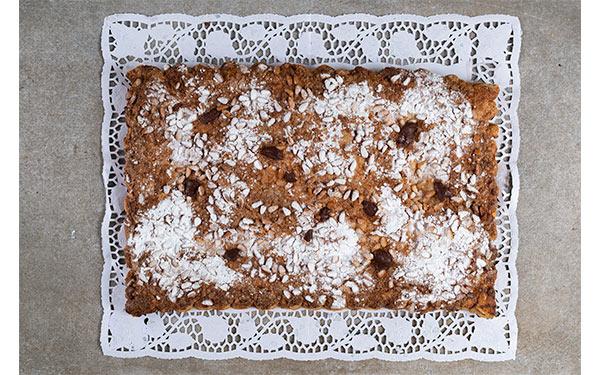 Hojaldre relleno de chocolate, cubierto de piñones y azúcar glass. Disponibles tres tamaños