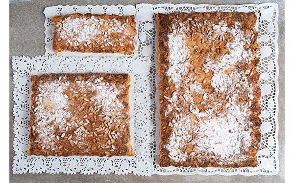 Hojaldre relleno de crema, cubierta de piñones y azúcar glass. Disponible en tres tamaños