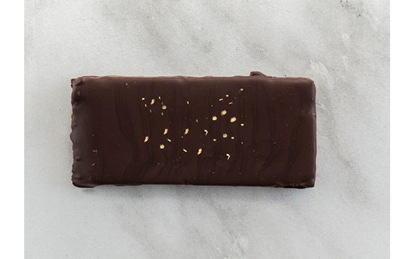 Trufado de chocolate negro Caribe de Valrhona 66%. Decorado con virutas de pan de oro.