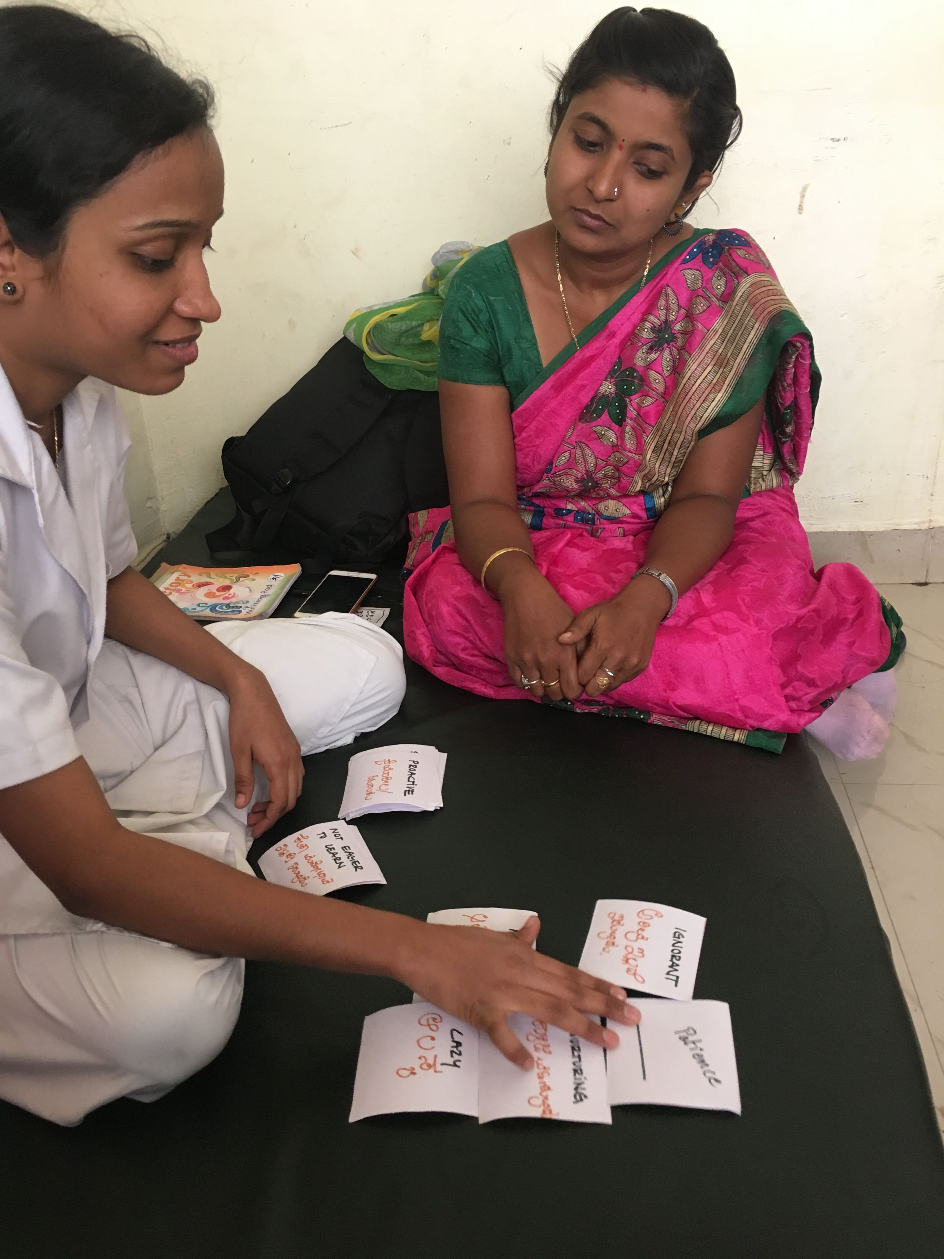 A woman uses paper cards as another woman looks on