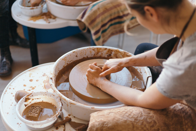 Woman sits at a potter's wheel making a pot