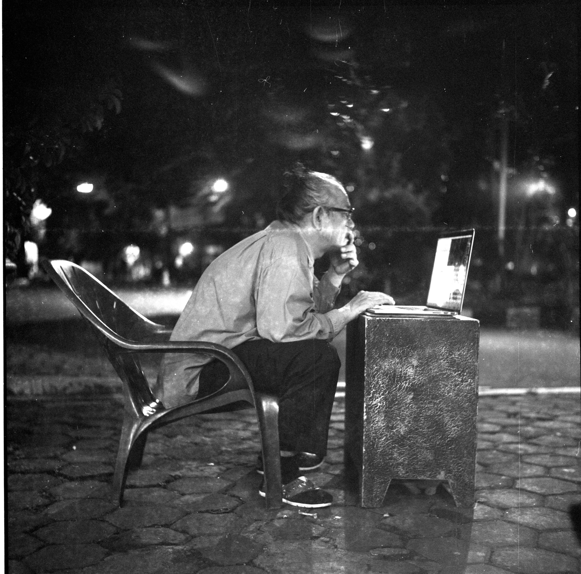 Black and white photo of a man users a computer on a street in Indonesia