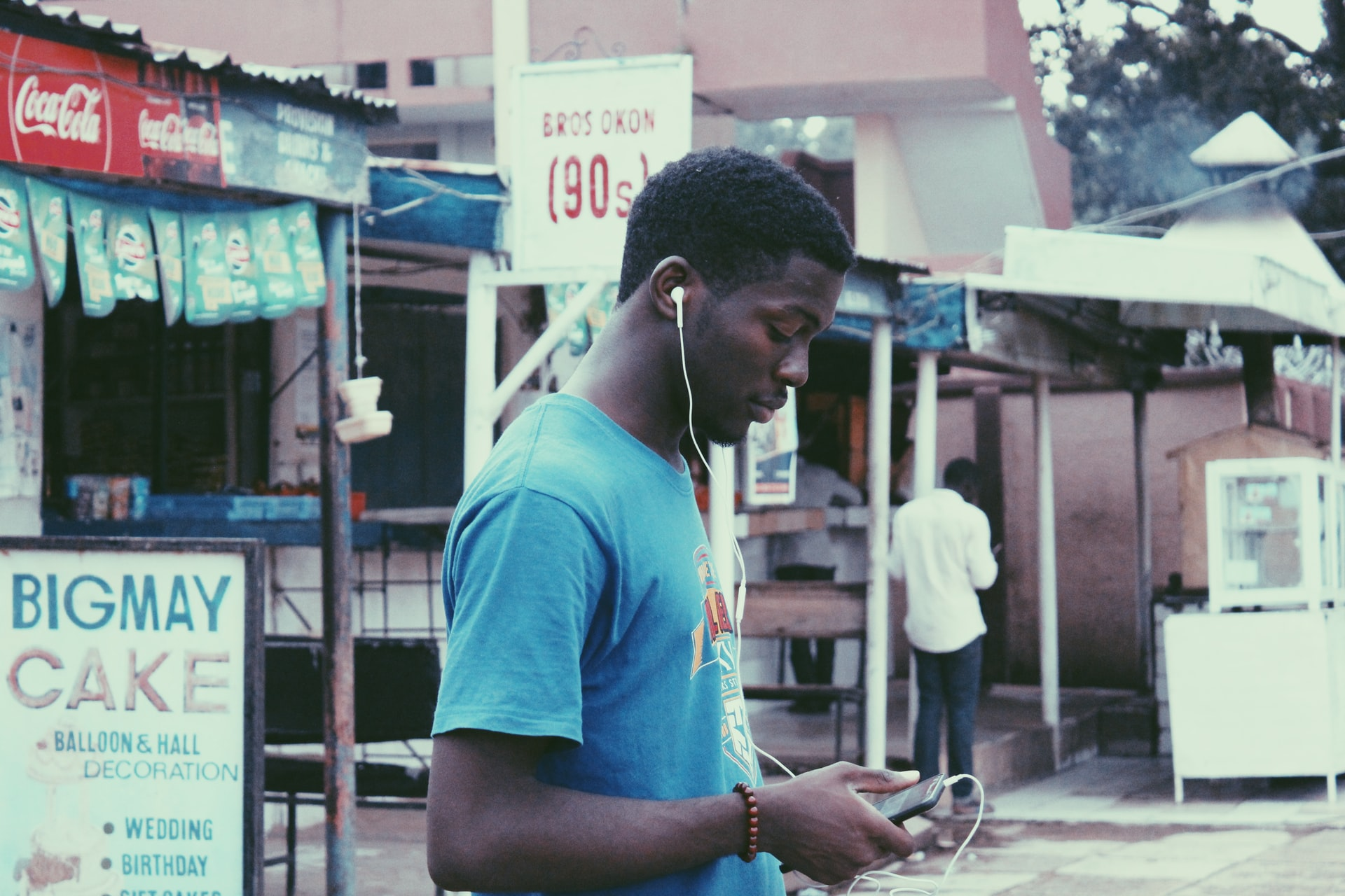 A man uses his smartphone with white earphones running to his ears