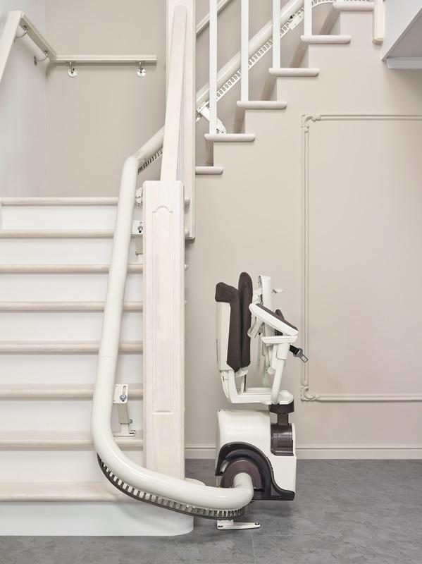 opgevouwen traplift stoeltje onderaan de trap