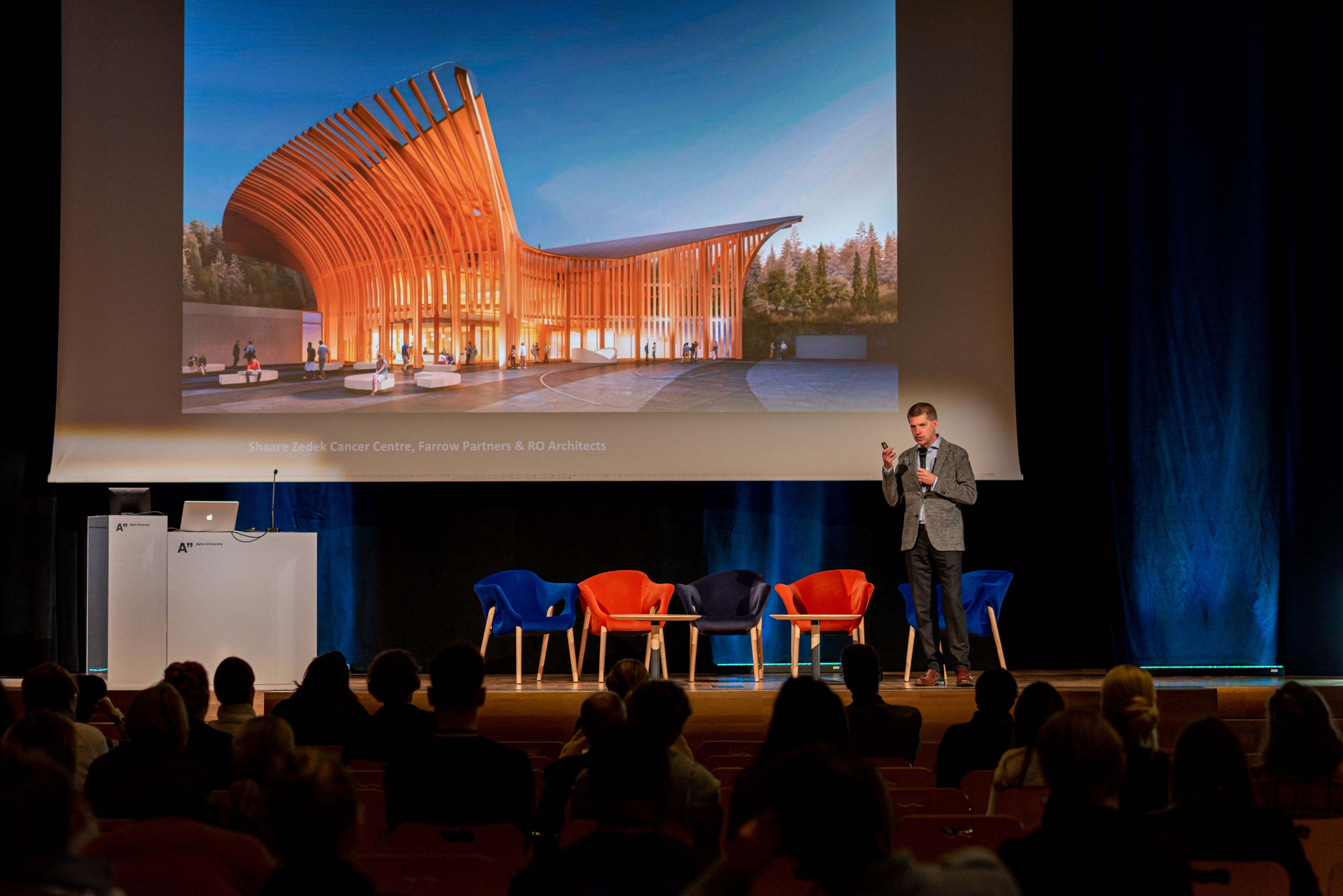 Keynote speaker Tye Farrow presenting architecture to a live audience at health design