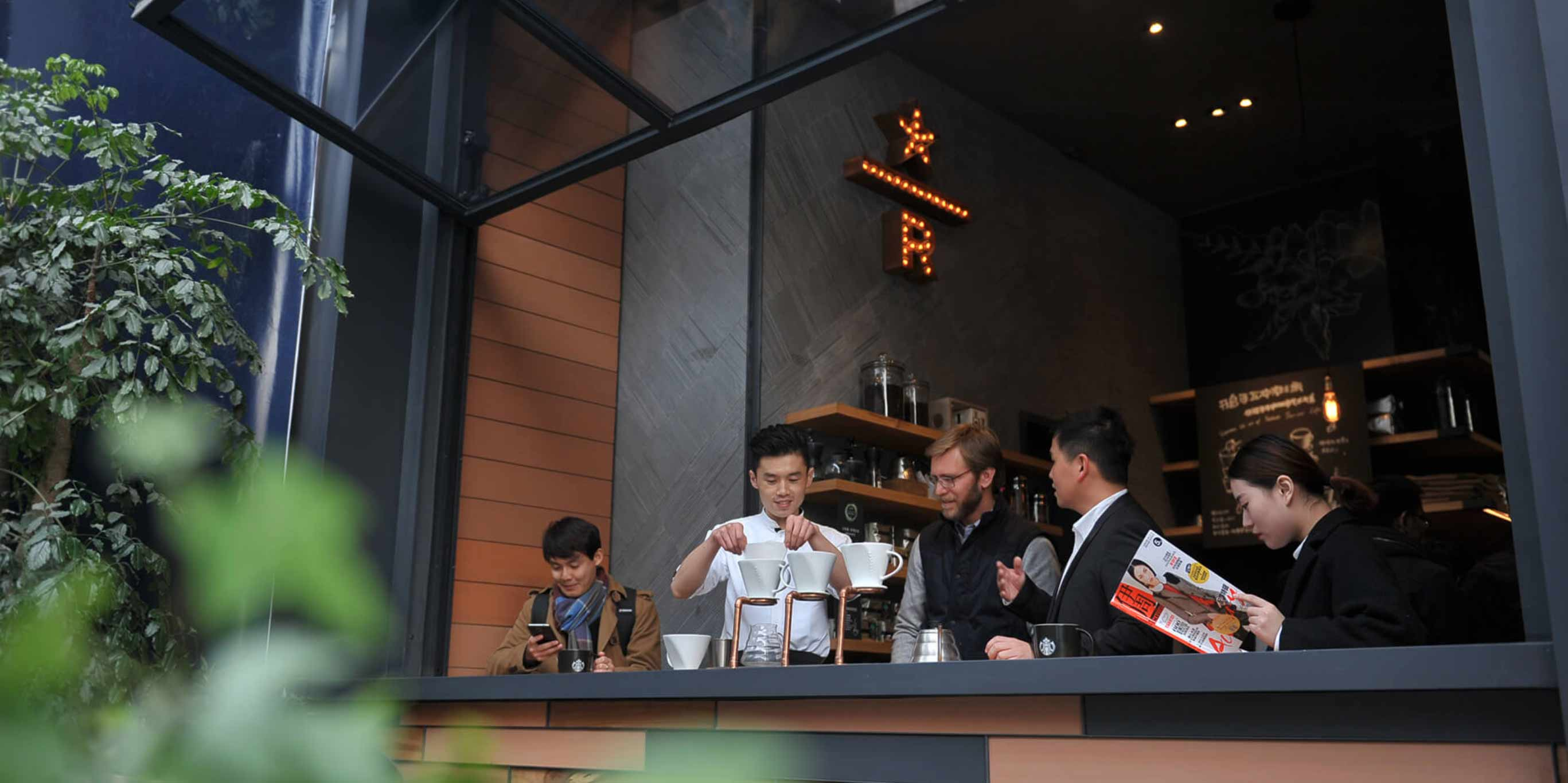 Image of Starbucks employee in China demonstrating pour-over coffee technique.